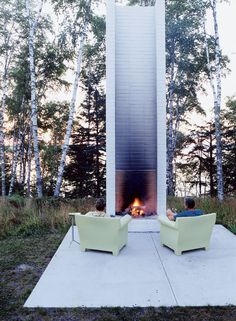 5 Modern Outdoor Living Areas | Dwell -- Seated on Philippe Starck's outdoor chairs for Kartell, homeowners Bruce Golob and Jean Freeman take in the warmth from the freestanding fireplace at their Two Black Sheds retreat on Wisconsin's Madeline Island.