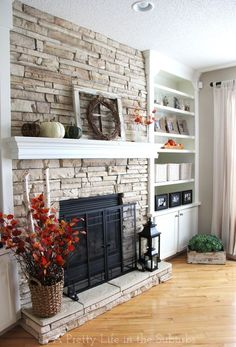 This is a decent representation of what I want our fireplace to look like EXCEPT - the colors (dark grey/black brick, cabinets to match the color in kitchen), and I would want the stone/fireplace to be build OUT a bit more, to make it stand out. Love the mantel over the stone!