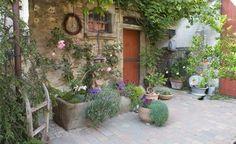 Mit Blumen bepflanzte Steintröge sind schöne Deko-Accessoires für Terrasse und Garten