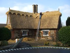 Trimming the ridge on a Reed roof.  Brian Mizon Thatching