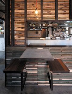 A timber partition, constructed from recycled fence palings, separates the bar from the booth seating