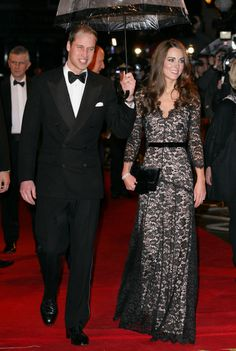 January 8, 2012: William and Kate attend the UK premiere of War Horse. Kate is wearing a black lace dress by Temperley and carrying a black velvet bow clutch by Mascaró.