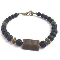 Mohawk Lava Bracelet Mohawk – a fashionable men's bracelet with black lava rock stones, antique bronze spacer beads and a rectangular copper centrepiece. Stylish and masculine this bracelet is finished off with an antique bronze lobster clasp. Black lava rock gemstones are a sign of of strength and courage.