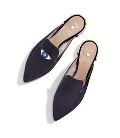 """Introducing the EYELOVE mules, a limited-edition collaboration between Stuart Weitzman and Gigi Hadid. Look Good, Do Good: This style represents our commitment to build three additional schools with Pencils of Promise, an organization dedicated to making quality education accessible to kids everywhere. The shearling-lined slides are available in two shades of suede, and they feature a single leather evil eye appliqué on the right shoe and a metallic heel detail. """"The evil eye is a powerful…"""