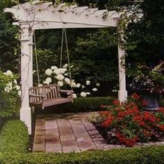 carve out a little quiet space in the corner of your backyard for a pergola painted white, a brick path and a swing.  perfect #landscapingandoutdoorspaces