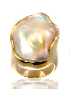 14kt yellow gold ring featuring one large, free form Ikecho pearl measuring 25 mm. The pearl features a white body color with excellent luster, orient and nacre thickness. The ring exhibits a high polished finish on the wide gold shank. This is a one-of-a-kind JA design.