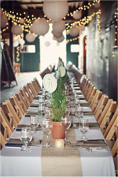 This is very similar to what i imagine for my wedding. long tables, burlap in the middle, lanterns and string lights. replace the plants with blue-green hydeangea in mason jars. exactly what i want