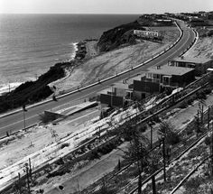 """Panoramic view of Pacific Coast Highway and area in Malibu in 1964. A billboard announces """"Sunset Mesa-New Homes for Sale."""" A multi-level apartment building is at right, and the ocean is at left. http://jpg3.lapl.org/pics35/00067318.jpg"""