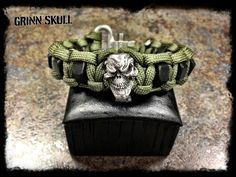 Silver grinning skull with black hex nuts and OD Green paracord.