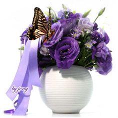 Vaso com flores roxas e borboleta batendo asas