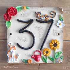 This beautifully hand made ceramic house sign is personalised with your own house number. I can replicate the design above with your cats, roses, a wee watering can and sunflowers or you can choose your own characters, colours and features!