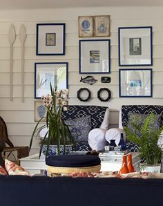A nautical inspired art wall incorporates found objects such as oars and decorative fish hangings in a blue and white color scheme....