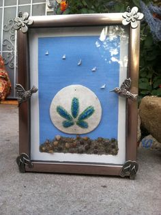 This was a fun project to make. I'm very please with how it turned out. Material include; frame which I purchased from the dollar store, metal embellishments from the corner craft store, glitter, glue, Modge Podge, paint brushes, sand dollar I collected from Sunset Beach, California, sand and pebbles I collected from San Gregario Beach in Half Moon Bay, California. I'm very happy with how it turned out.