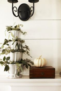 Sophisticated decor  Let autumn colors, fall foliage and Halloween fun inspire your mantel decorations.   Tiered white containers brim with seeded eucalyptus, while a wooden chest and small white pumpkin bring offer interesting shapes and muted colors to this sophisticated mantel.