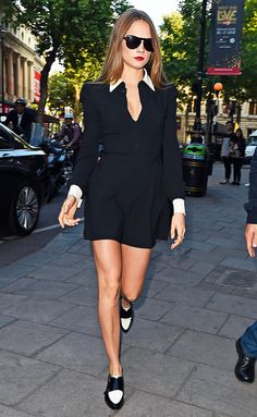 Cara Delevingne wears a collared black dress with black and white shoes and black sunglasses