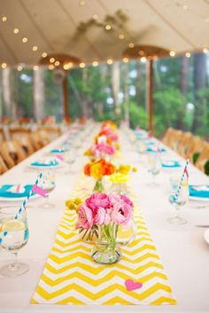 super simple: long stretch of rectangular tables, white table cloths, long runner down center, clumps of vases every 6-8 ft. with single blooms