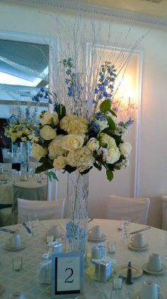Wedding centerpiece of white hydrangea, white roses, blue delphinium and white birch branches atop clear glass cylinder filled with delphinium and birch branches.  Doristhefloristt.com