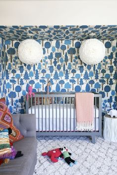 Fantastic nursery with blue forest wallpaper covering walls and ceiling of nook accented with a pair of white flower pendants