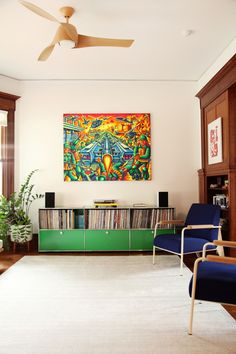 The record cabinet is by   USM Haller .  The large war painting is a traditional sound system Pico painting Danielle had commissioned in Columbia . The ink blue chairs are   Prouvé Fauteuil  de salon lounge chairs  from  Vitra.