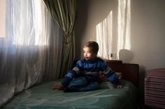 A child gazes out of a window at an orphanage in Homs