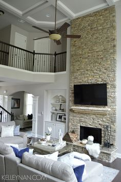 two story great room | stacked stone fireplace | rock fireplace | coffered ceiling | neutral living room | built-ins | neutral living room fall decor