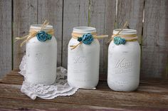 3 hand painted mason jars, done in white, lightly distressed, wrapped with a twist of raffia, papercraft flowers, and a protective coating. They are not painted on the inside and can hold water for fr