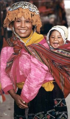 South America | Portrait of a Quechua woman in traditional clothing carrying her child, Peru
