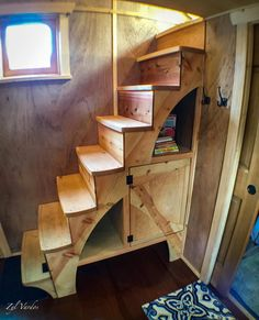 A custom storage staircase leads to the bedroom loft and a built-in couch slides out to become a full size bed.