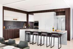 Elegante design di cucina moderna con mobili in bianco lucido e rovere scuro e piano lavoro in cemento