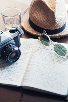travel essentials : notebook, panama, sunglasses, canon camera