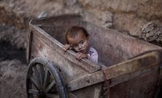 Islamabad, Pakistan: A child, with his face covered with flies, sits inside a wooden cart