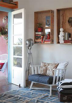 Na parede, caixotes de peixe, tratados com verniz náutico fosco, servem de prateleira. Almofadas de Ana Luiza Wawelberg e tapete da Oka Design.