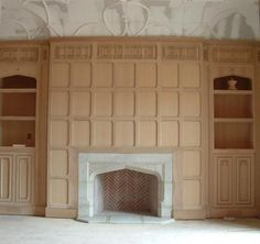 Tudor arch fireplace mantel surrounded by paneling & built-in bookcases -- Tudor Artisans