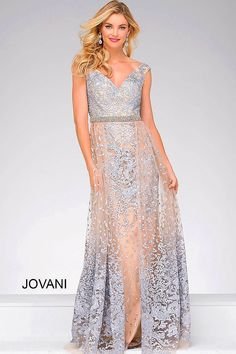 Silver lace over nude lining floor length off the shoulder prom dress features v neckline, embellished belt and an overskirt.