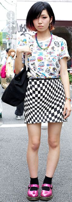 girl in a retro pinup print top, an op art checkerboard skirt that's a remake & metallic Mary Jane shoes from Dr. Martens!