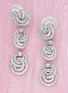 CARTIER A Rare pair of diamond Earpendants, circa 1950 Designed as a series of graduated circular and baguette-cut diamond spiral motifs, mounted in platinum, length 8.4 cm.   Signed 'Monture Cartier'  With jeweler's mark and numbered and french assay marks