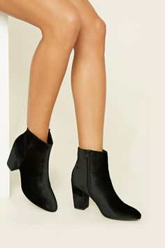 A pair of velvet ankle booties featuring a block heel, pointed toe, and a side zipper.