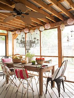 This screen porch sounds as charming as it looks with a new tin roof that captures every pitter-patter of rain. A collection of mix-and-match bistro chairs provides plenty of seating around the rustic wood table. A candelabrum chandelier, paper lanterns, and leaf ceiling fan set the mood from dawn through dusk.