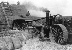 "Men working threshing corn into hay using a steam traction engine - a Burrell 7 NHP single crank compound engine with Crayton and Shuttleworth 4'6"" threshing machine, belonging to James Penfold Ltd. Farmer Henry Tupper is standing by the smokebox. Wheel and driving belt. ImageDate 	1948"