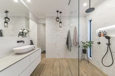Contemporary style bathroom example with large marble slabs wood floors and black accents. Contemporary Style Bathrooms, Contemporary Ceramics, Bathroom Styling, Bathroom Lighting, Concrete Look Tile, Marble Tiles, Marble Slabs, Solid Surface Countertops, Wood Bathroom