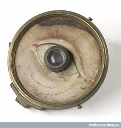 eye defect teaching model, glass lens with brass-backed paper front with hand-painted face around eye, by W. and S. Jones, London, 1840-1900