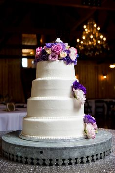 Gorgeous purple wedding cake!!  Love the simple white of the round cake tiers, and the gorgeous pop of color from the floral cake topper//additions.  Perfect wedding cake for a purple wedding! Taken at THE SPRINGS Event Venue in Edmond, OK. #lavenderweddingcake #purpleweddingcake #simplepurpleweddingcake #elegantpurpleweddingcake #purpleweddingideas #purplewedding