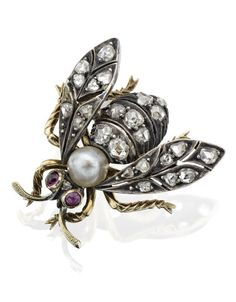 A late Victorian gem-set bee brooch.  Realistically modelled, set throughout with rose-cut diamonds, the body a 4.50mm pearl, the eyes of circular cabochon-cut rubies, mounted in silver and gold, length 20mm, pearl untested, to original fitted case