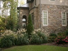 Miscanthus sinensis 'Adagio,' Encore azaleas and Prunus laurocerasus 'Otto Luyken' soften the stone on the classical European-style home, which has an arched entryway.