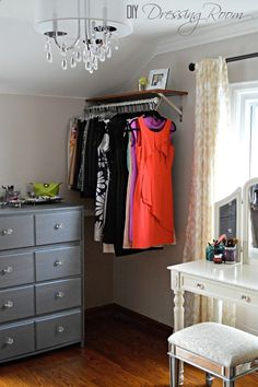 Inexpensive dress room. Check out this gorgeous converted bedroom makeover--- vanity in front of window, vintage lighting, garment racks, small dresser w/ vanity tray, build in laundry sorter