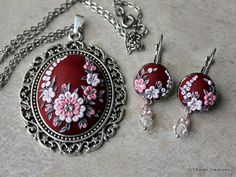 Lovely pendant with floral design in beautiful shades of pinks, whites and greys on maroon cabochon, ornamented with rhinestones. It is hand sculpted from scratch with polymer clay using the applique technique. The cabochon is mounted on oval antique silver finish pendant.  The pendant is 46x61 mm (1.8x2.4 inches) while the cabochon is 30x40 mm (1.5x1.1 inches). The pendant comes with a 18 inches (45.7cm) long chain.  *P.S: This listing is only for the pendant and chain. The matching earings…