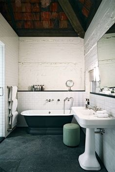 Lofts Soho House Berlín Bañera exenta negro mate, azulejos de metro y vigas en el techo: un baño con factura nostálgica.