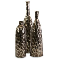 Exotic and chic, the Bevan Ceramic Vases are adorned with a diamond relief pattern in a subtle metallic bronze glaze. Mix these organic, modern shapes with natural materials for an eclectic style statement. Set of three.