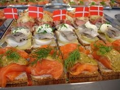 A tray of Smørrebrød. Smoked salmon the front. Herring, onions & egg in the center. Danish flags are a nice decorative touch!