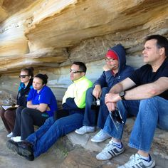 The crew of new PADI Instructors listening to a dive brief under the sandstone cliffs.